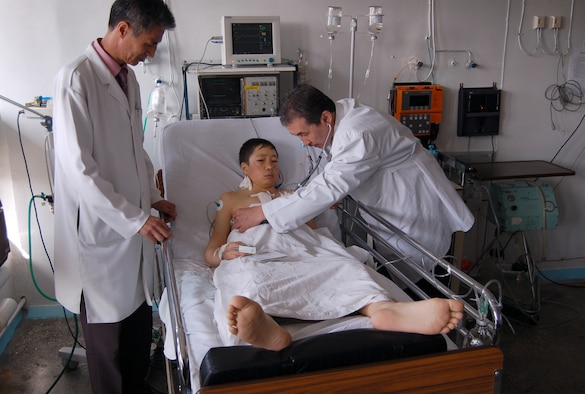Dr. Samudin Shabyralie, heart surgeon in the local Institute of Cardiac Surgery and Organ Transplantation and Dr. Kaldarbek Abdramanov, Director and professor of surgery check on the Manas Air Base Outreach Society-sponsored 100th heart surgery patient, Alymbekov Amanbek, Saturday in the Children's Heart Ward. (Air Force photo by Tech. Sgt. Jerome Baysmore)
