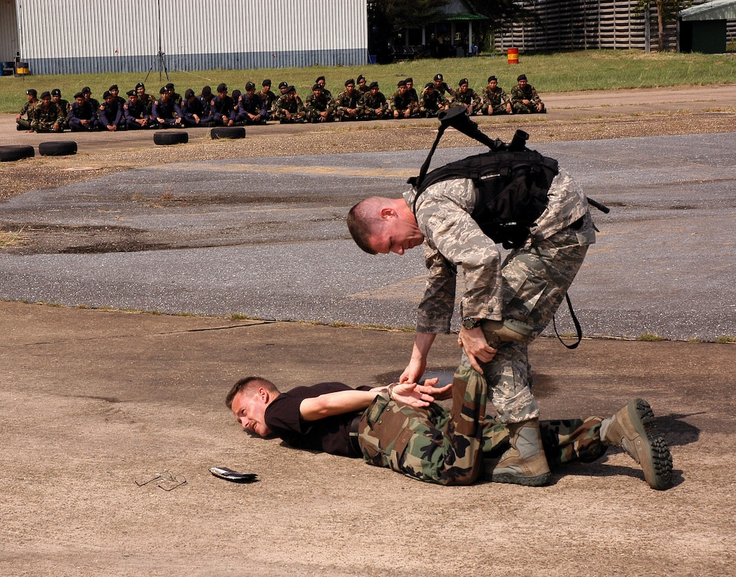 Staff Sgt. Richard Holder cuffs Tech. Sgt. Gregory Stout during exchange training with ground defense forces from Udon Thani, Thailand. Sergeant Holder is assigned to the 18th Security Forces Squadron at Kadena Air Base, Japan.  Sergeant Stout is assigned to the 353rd Special Operations Group security forces at Kadena AB. (U.S. Air Force photo/Master Sgt. Marilyn Holliday)