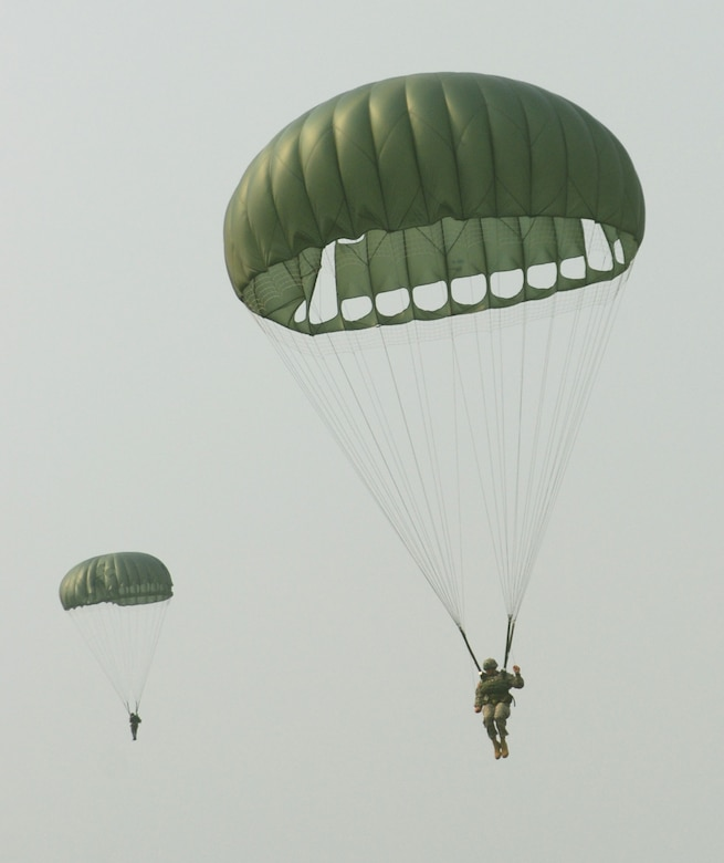 Paratroopers descend over the drop zone at Soto Cano Air Base, Honduras, during a combined airborne operation April 30. The operation was part of a week-long idea exchange between U.S. and Honduran soldiers. (U.S. Air Force photo by Tech. Sgt. John Asselin)