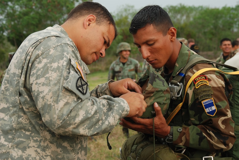 """Capt. Charles Faison, 509th Airborne Battalion, Ft. Polk, La., helps a Honduran """"paracaidista"""" repair his helmet before the combined jump with U.S. and Honduran soldiers April 30. The 509th was in Honduras to exchange ideas with Honduran military members in preparation for a multi-national exercise in August. (U.S. Air Force photo by Tech. Sgt. John Asselin)"""
