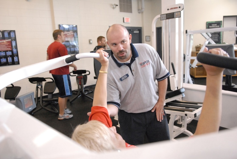 Scott Peavy, a recreational assistant at the Fitness Center, works with a patron. Mr. Peavy is one of six personal trainers who help patrons get the most out of their workouts. U. S. Air Force photo by Raymond Crayton