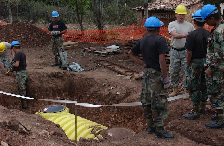 LAS MESAS, HON - Officer Candidate, Staff Sgt. Martin Berta, 322nd Engineer Company, Decorah, Iowa,  explains to Honduran army engineers how the newly laid septic tank functions here April 16. Photo by Staff Sgt. Danny McCormick, Beyond the Horizon public affairs.