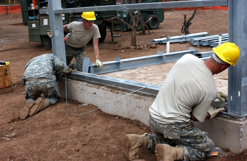 LAS MESAS, HON - Spc. Jesse Brennan (right), Spc. Dustin Roberts (ACU) and Sgt. Gabriel Feuerhelm, all of the 322nd Engineer Company, Decorah, Iowa, attach a bottom brace to the steel framework wall of a new latrine that they are building here April 16. Photo by Staff Sgt. Danny McCormick, Beyond the Horizon public affairs.