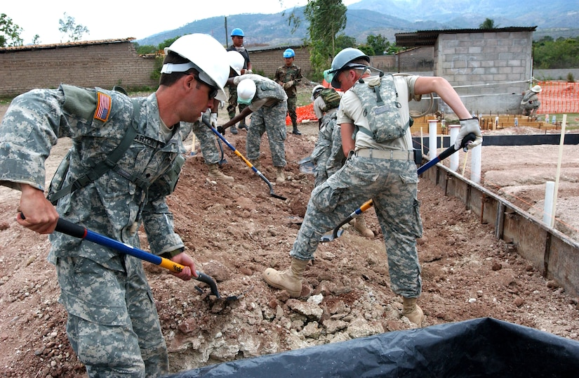 LA MERCED, HON - Soldiers from both the U.S. and Honduran armies work together shoveling dirt to place against framing before cement can be poured for the foundation of a new school here April 16. Photo by Staff Sgt. Danny McCormick, Beyond the Horizon Public Affairs.