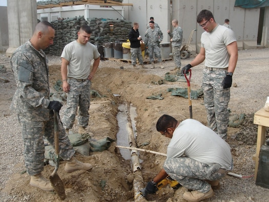 (From left) Tech. Sgt. John Becquer, Airman 1st Class Matthew Giacona and Staff Sgt. Caleb Dennis, all from the 732nd Expeditionary Civil Engineer Squadron Detachment 6, watch as Staff Sgt. Pranay Singh, a utilities craftsman also with Det. 6, cuts through a drain pipe. The pipe will carry  water to the showers, clothes washers and kitchen at Patrol Base Olson, Iraq. The Airmen are assigned to the 18th Civil Engineer Squadron here. (U.S. Air Force photo)