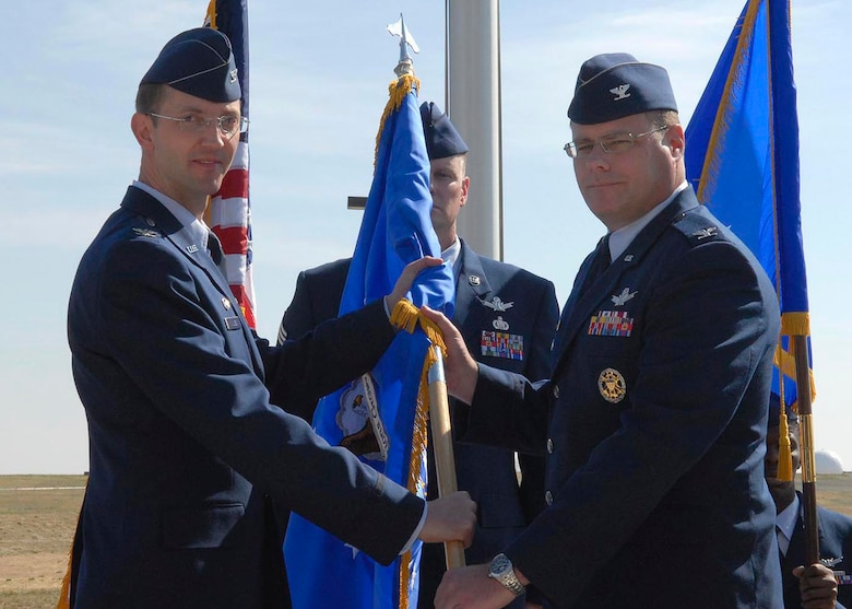 BUCKLEY AIR FORCE BASE, Colo -- Col. Wayne McGee, 460th Space Wing commander, passes the 460th Operations Group guidon -- during the group's change of command -- to Col. Richard Schoonmaker. Colonel Schoonmaker assumed command of the 460th OG April 30. (U.S. Air Force photo by Senior Airman Steve Czyz)