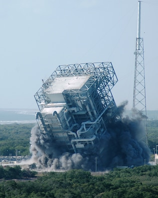 The mobile service tower at Space Launch Complex 40 raises a cloud of dust and smoke as it falls to the ground at Cape Canaveral Air Force Station April 27. The obsolete tower was demolished to make way for new launch programs at Cape Canaveral. (U.S. Air Force photo by Airman 1st Class David Dobrydney)