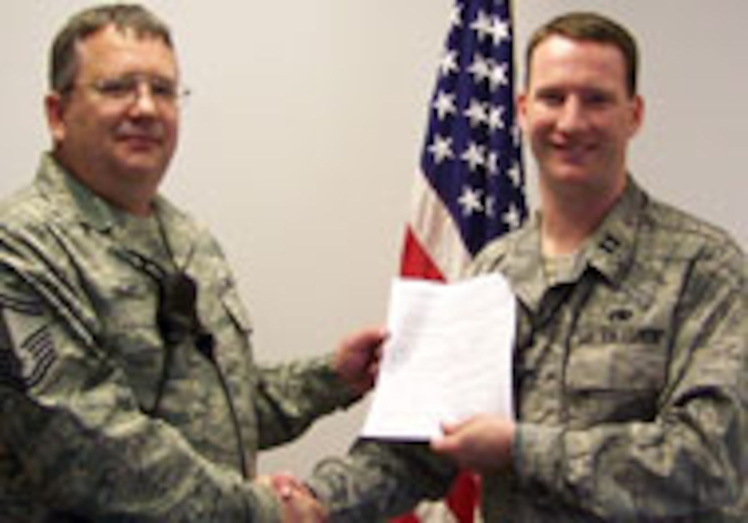 Pro-Super SMSgt Jeff Drake re-enlisted with Capt Nick Lotito AMXS AMU OIC