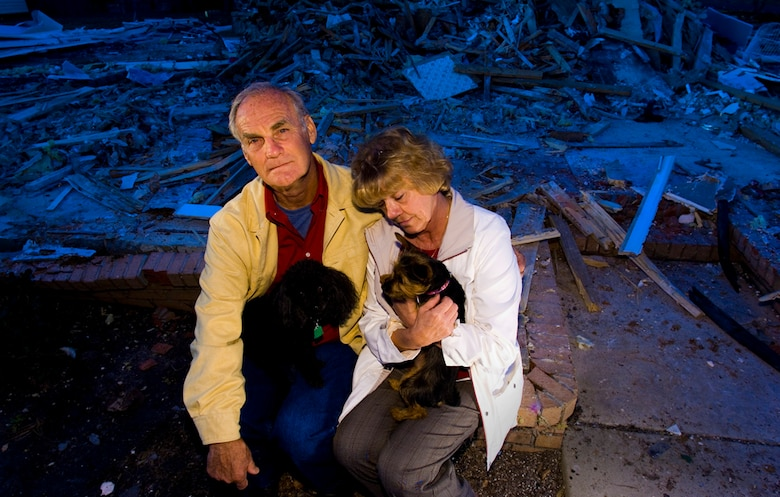 With their dream home reduced to a nightmarish rubble, Wayne and Ilah Glover, with their dogs Bailey and Izzie, say they will rebuild, a process that could take up to nine months. (Photo by Tech. Sgt Matthew Hannen)