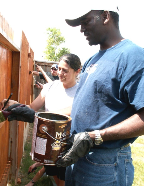 Tech. Sgt. Becca Dahl (left) and Master Sgt. Ken Pittman (right), personnelists at the Air Force Personnel Center, Randolph Air Force Base, Texas, apply waterproofing to a fence as part of a volunteer effort supporting Operation Homefront. Volunteers from AFPC's Junior Enlisted Council and Top 3 Association helped stain fencing and built a gate to provide better access between the front and back yards for Tech. Sgt. Israel Del Toro, an Airman recovering from wounds sustained during a roadside bombing in Afghanistan, December 2005. (US Air Force photo/Master Sgt. Kat Bailey)
