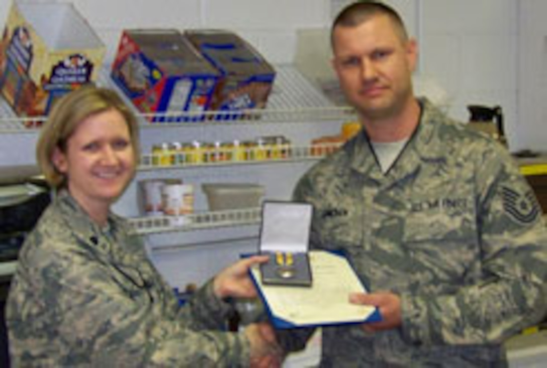 Flightline Avionics Specialist Technical Sergeant Stephen Smolen receives the Air Force Commendation Medal from Lt. Col. Catherine Hutson, AMXS Commander.