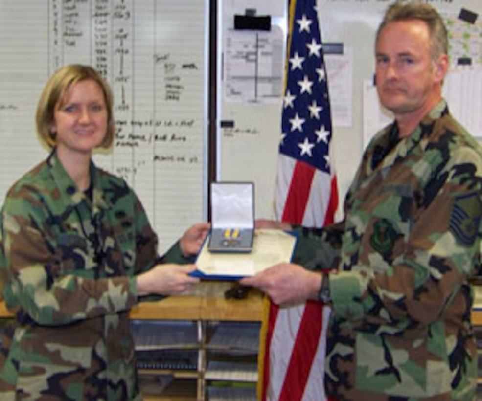 F-16 Crewchief Master Sergeant Fitzpatrick receives the Air Force Commendation Medal from Lt. Col. Catherine Hutson, AMXS Commander.