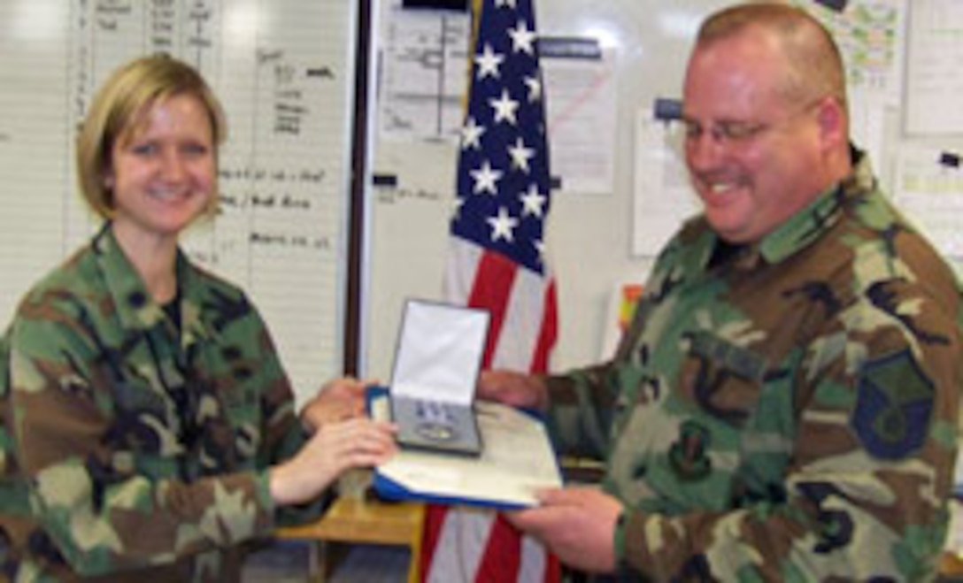 F-16 Crewchief Master Sergeant Edward Ashcraft receives the Air Force Achievement Medal for outstanding service while deployed to Balad AB, Iraq from Lt. Col. Catherine Hutson, AMXS Commander.