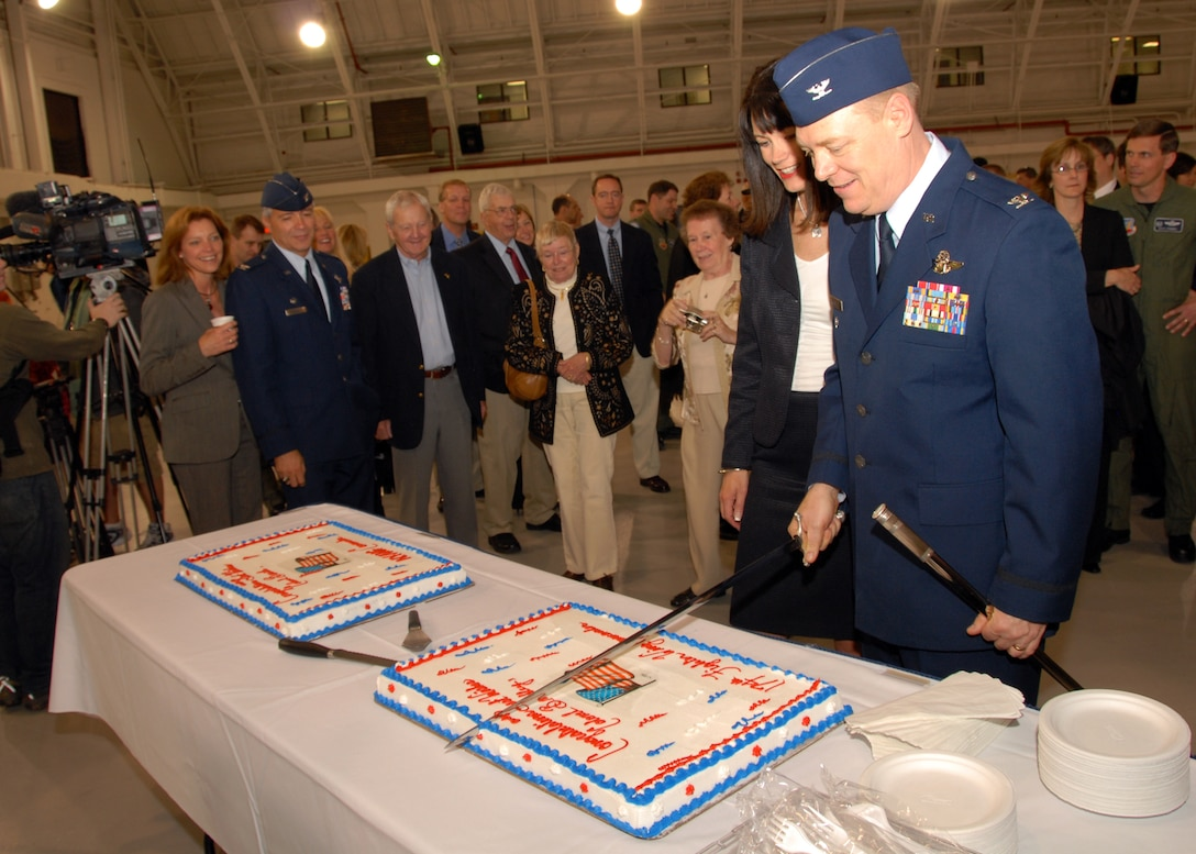 Col. Kevin W. Bradley and his wife Karen prepare to cut his congratulatory cake as all of his well wishers gather around.