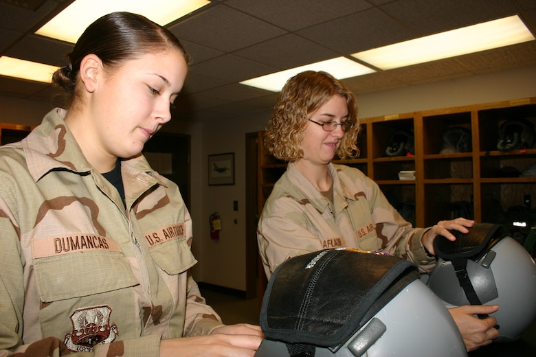 Airman 1st Class (A1C) Leilani Dumancas and Airman (Amn) Kari Raaflaub of the 148th Fighter Wing, Duluth, Minn. Air National Guard, Life Support Shop repair helmets at their desk inside the Operations building on January 20, 2007.  A1C Dumancas and Amn Raaflaub were cleaning and repairing the equipment prior to a training flight.  (U.S. Air Force photo by Senior Airman Donald Acton)(Released)