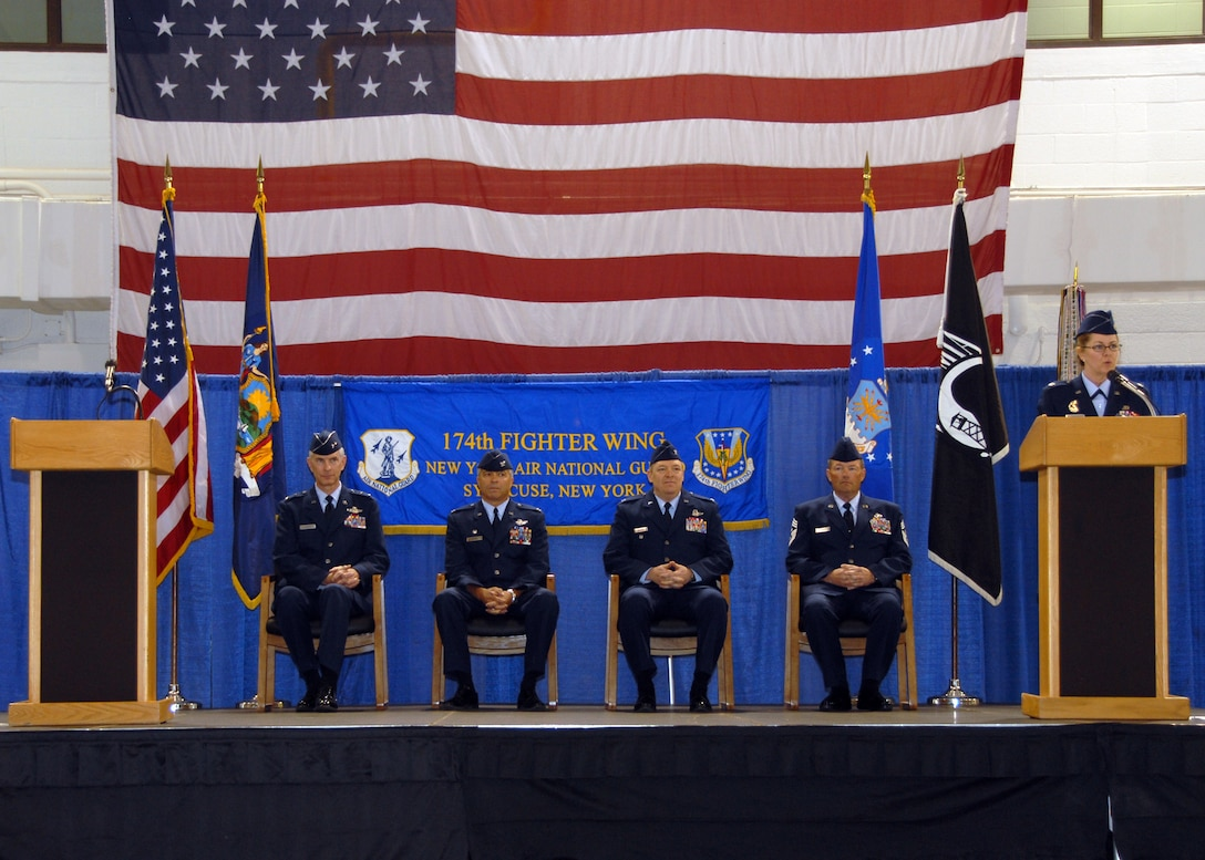 Lt. Col. Maryjo Timpano, 174 FW Executive Officer addresses the assembled crowd during the 174 FW Change of Command Ceremony. On stage is Maj. Gen. Robert A. Knauff, Col. Anthony B. Basile, Col. Kevin W. Bradley and Command Chief Master Sergeant David D. Heckman.