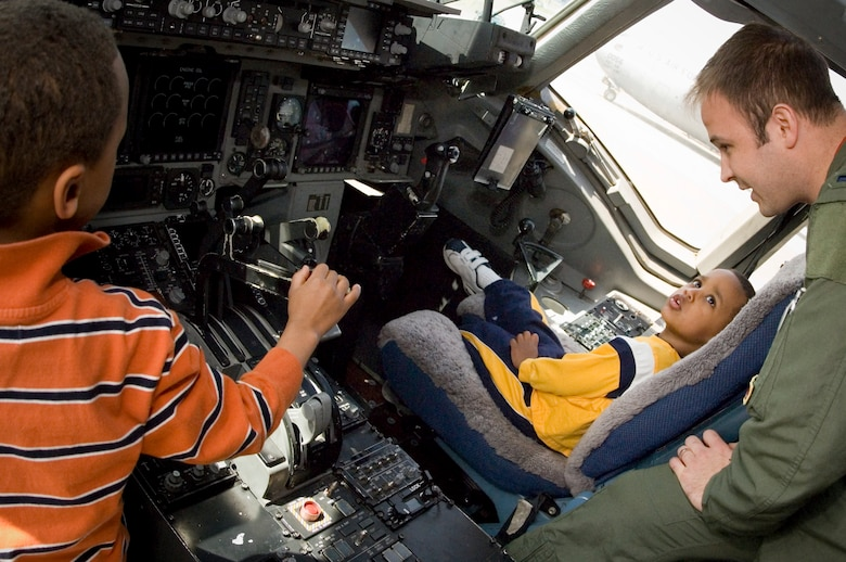 Jeremiah Lani, 2, sits in the pilot's seat and listens as 1st Lt. Zachary Dorman, 10th Airlift Squadron, explains the flight deck controls.