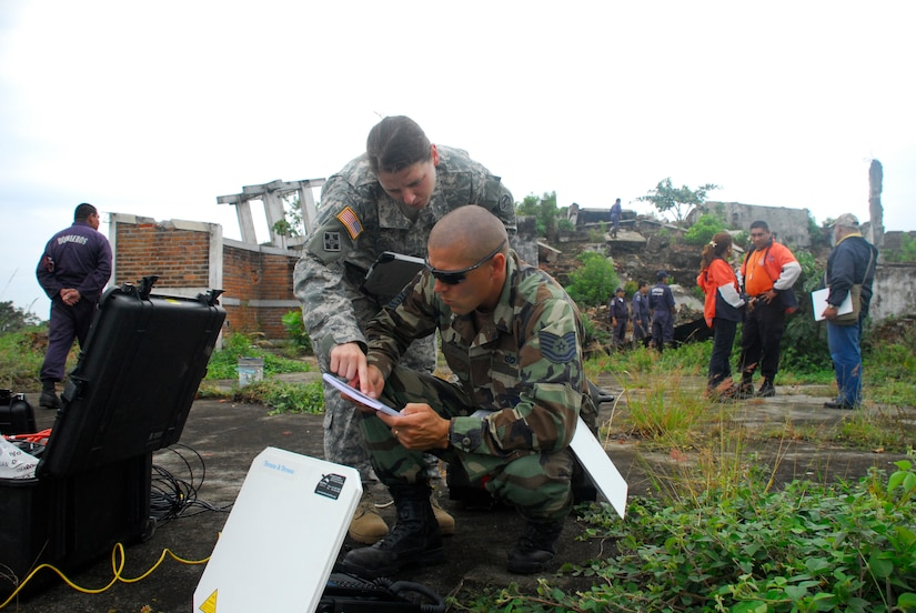 From the grounds of a collapsed and abandoned coffee factory, Joint Task Force-Bravo civil engineers Air Force Tech. Sgt. Mike Vaughn and Army Capt. Sarah Williams set up a field video teleconferencing unit to send imagery gathered here to the United States to assist with the exercise Fuerzas Aliadas Humanitarias 2008, a regional disaster relief exercise involving military and civilian agencies occurring here May 5-15. By capturing imagery of damage from a 2001 earthquake, participants in the exercise have a simulated yet realistic view of damage to help them make accurate decisions regarding the relief process. (U.S. Air Force photo by Tech. Sgt. William Farrow)