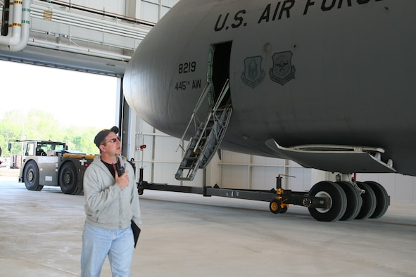 WRIGHT-PATTERSON AFB, Ohio - Master Sgt. Doug Werner, 445th Aircraft Maintenance Squadron, is on the radio as a C-5 Galaxy is pulled for a fit test into the third and final hangar to be completed as part of the 445th Airlift Wing's large construction project to support the C-5 aircraft since their conversion began.  This hangar includes staff, shops, and tool crib areas used primarily for scheduled maintenance. (U.S. Air Force photo/Mary Allen)