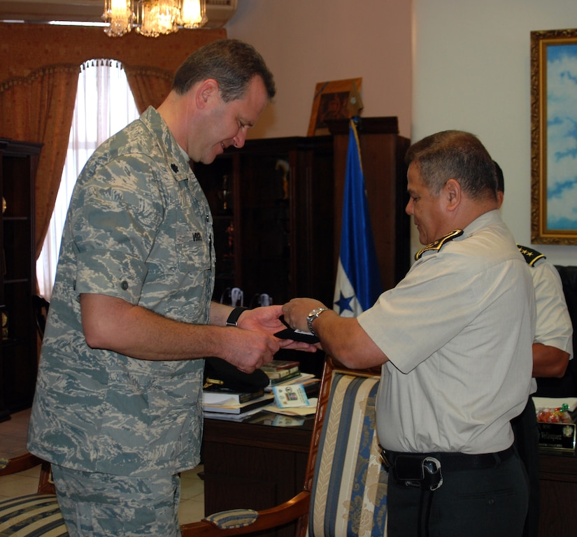 Air Force Lt. Col. Randall Vogel, 612th Air Base Squadron commander, receives a coin from Honduran Chief of Defense, General de Division Romeo Orlando Vasquez Velasquez, during a ceremony May 5 in Tegucigalpa Honduras. Colonel Vogel and two others from JTF-Bravo receved Honduran Medals of Merit earlier in the morning.