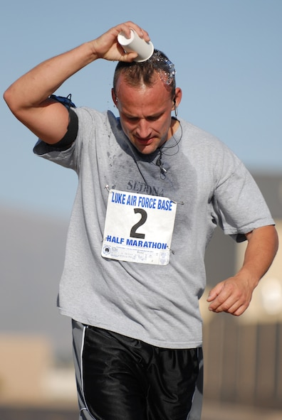 Technical Sergeant Mark Aube, an electrical environmental technician with the 309th Aircraft Maintenance Unit, cools off with a cup of water during the half marathon held at Luke Air Force Base, Ariz., May 3. Fifty four runners logged more than 700 miles during the Saturday run.(U.S. Air Force Photo/ Staff Sergeant Jerry Fleshman)
