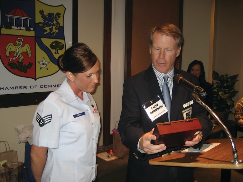 "Senior Airman Jennifer Booth receives a gift box from Larry Hammond, vice chairman of the New Braunfels, Texas, Chamber of Commerce during a reception honoring her as Randolph Airman of the Year for 2007. The engraving on the box said, ""Leadership: Leaders are like eagles; they don't flock. You find them one at a time."""