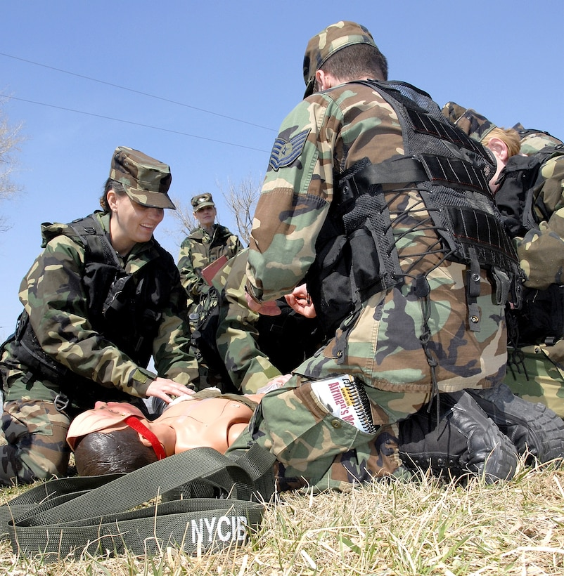 """Air Force reservist Tech. Sgt. Angela Harroun, 710th Medical Squadron, and her team administer aid to a wounded """"victim"""" during a field-training exercise at Offutt Air Force Base, Neb., as her commander, Col. Joan Gonzalez, observes the activities. The 710th is an Air Force Reserve Command squadron based at Offutt and is a geographically-separated unit assigned to the 442nd Fighter Wing at Whiteman AFB, Mo. (US Air Force photo/ Master Sgt. Bill Huntington)"""