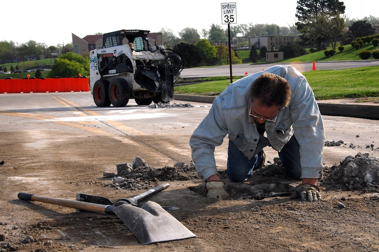 Mike Wollery, a maintenance and equipment staff member from the 55th Civil Engineer Squadron, removes broken concrete from a pot hole near the corner of SAC Boulevard and Peacekeeper Drive here May 6. The Civil Engineer Squadron is working hard to repair the roads on Offutt after a brutal winter. (U.S. Air Force Photo By/Josh Plueger)