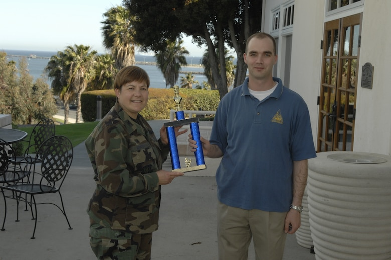 Tech. Sgt. Robert Bucholtz accepts the AFSPC's MAJCOM Chess Tournament's second place trophy from Col. Nannette Benitez, 61 MSG Commander. He advances to the Air Force Chess Championship, May 5-8. (Photo by Stephen Schester)