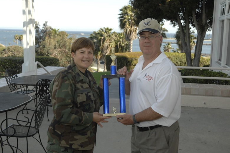 Lt. Col. Douglas Taffinder accepts the AFSPC's MAJCOM Chess Tournament's first place trophy from Col. Nannette Benitez, 61 MSG Commander.  Lt. Col. Taffinder is the 2007 Inter-Service Chess Champion.  He advances to the Air Force Chess Championship, May 5-8. (Photo by Stephen Schester)