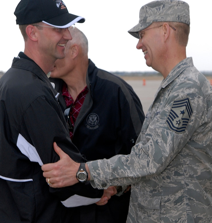 """PETERSON AIR FORCE BASE, Colo. -- Col. Wayne McGee, 460th Space Wing commander, is greeted by Chief Master Sgt. Richard Small, Air Force Space Command command chief, May 7 on the Peterson Air Force Base flightline. Guardian Challenge team members descended upon the southern Colorado base as the teams prepared for three days of events, including a golf tournament, space and missile forum and an awards and dinner banquet May 9. The Guardian Challenge competition pits the command's several space wings against each other to see whose the """"best of the best"""" in areas of expertise, including security forces, communications, missile combat and satellite operations. (U.S. Air Force photo by Mr. Dennis Howk)"""