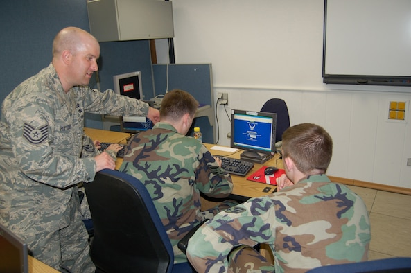 Tech. Sgt. Robert Pletcher (standing) and Tech. Sgt. Derron Cockayne, both assigned to the 1st Air and Space Communications Operations Squdron, demonstrate TBMCS-UL classroom preparation procedures to newly assigned Senior Airman Thomas Callan.(Courtesy Photo)