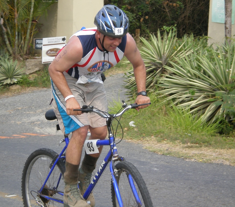 Air Force Capt. Manny Silveira, a Joint Task Force-Bravo participant in the Bay Islands Triathlon, climbs a hill during the bike portion of the competition May 5. Twenty-eight JTF-Bravo personnel competed in the event with all completing the race.