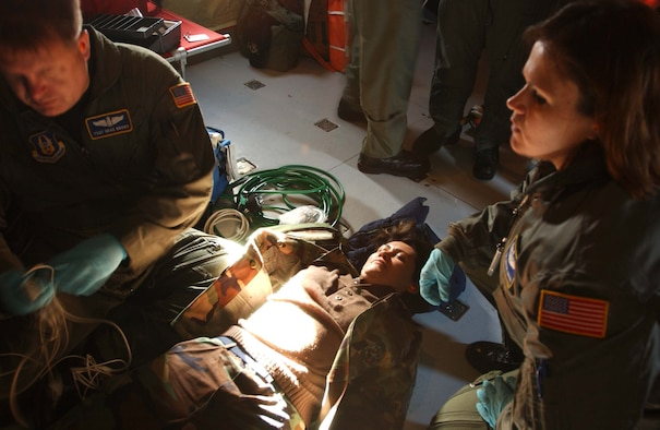 ST. CROIX, U.S. VIRGIN ISLANDS -- Tech. Sgts. Grae Brown and Crystal Drake, 459th Aeromedical Evacuation Squadron medical technicians, administer care to simulated patient Master Sgt. Patty Guzman-Evans, 459th AES first sergeant, during an in-flight exercise. Ten members of the 439th AES joined 459th AES members in a blended AE training mission to the island. Mission training expanded beyond the medical realm to include air refueling and an overseas sortie. (U.S. Air Force photo/Staff Sgt. Amaani Lyle)