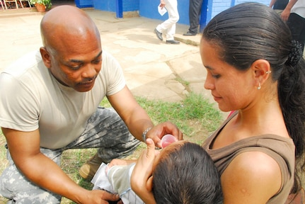 COMASAGUA, El Salvador ? Army Staff Sgt. Alfred Wyatt gives anti-parasitic medicine to a young Slavadoran boy May 8 at a school near Comasagua, El Salvador, during Fuerzas Aliadas Humanitarias 2008, the U.S. Southern Command and Salvadoran Ministry of Defense-sponsored exercise held throughout the Central American region May 5-15. (U.S. Air Force photo by Tech. Sgt. William Farrow)