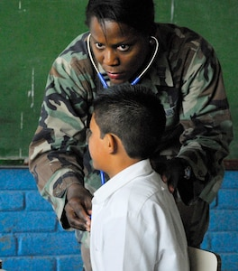 COMASAGUA, El Salvador ? Air Force Capt. Charlene Kirby examines a Salvadoran boy May 7 at a school near Comasagua, El Salvador, during Fuerzas Aliadas Humanitarias 2008, the U.S. Southern Command and Salvadoran Ministry of Defense-sponsored exercise held throughout the Central American region May 5-15. Captain Kirby was part of the 18-person team of Soldiers and Airmen from Soto Cano Air Base, Honduras, who spent two days operating a makeshift clinic at an elementary school triaging more than 1,600 Salvadoran villagers. (U.S. Air Force photo by Tech. Sgt. William Farrow)