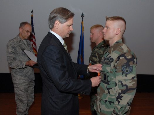 North Dakota Governor John Hoeven pins the Air Force Combat Action Medal on Staff Sgt. Aaron D. Giere, of the 119th Detachment 2, right, at the Minot Air Force Base, May 13.  Master Sgt. Dominic A. Cook, of the 119th Detachment 2, is also presented the Air Force Combat Action Medal by Gov. Hoeven who is assisted by Brig. Gen. Patrick L. Martin, the North Dakota National Guard assistant adjutant general for air.   iere and Cook recieved the medal in recognition of actively participating in combat operations while serving in Iraq in 2003. The AFCAM has only been awarded to two other members in the history of the N.D. Air Guard; Cook and Giere are the first to receive it for the Air Guard Detachment in Minot. (U.S. Air Force photo by Senior Master Sgt. David h. Lipp) (RELEASED)