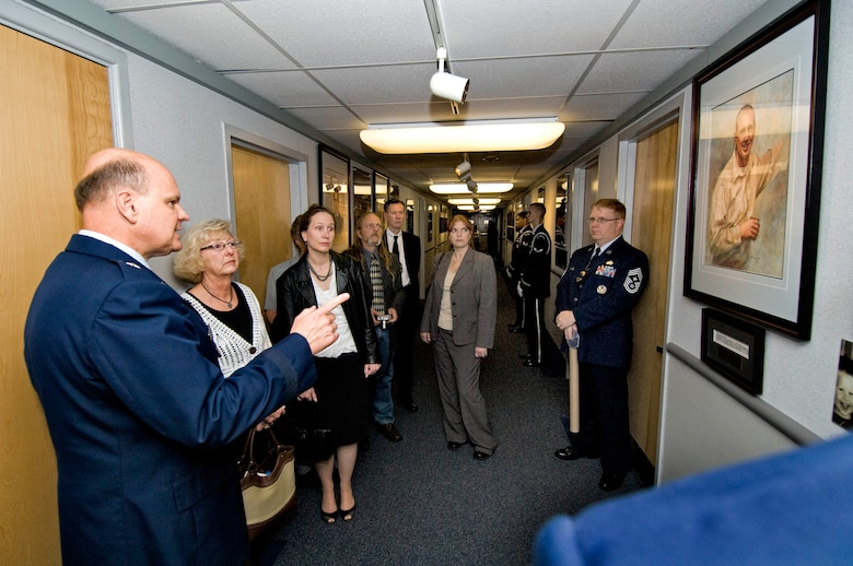 Brigadier General Dana Simmons, commander, Air Force Office of Special Investigations, tours the AFOSI Hall of Heroes with family members of Special Agent Thomas Crowell. (U.S. Air Force photo/Mike Hastings)