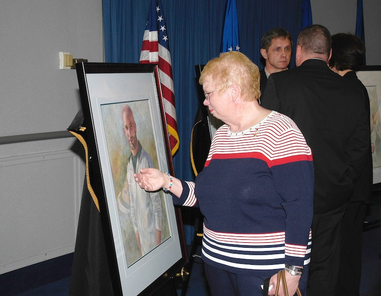 Lorraine Wieger, mother of Special Agent David Wieger, stops to touch a portrait of her son who was killed in Iraq on November 1, 2007. A portrait of SA Wieger and four other special agents were dedicated May 13 in the Headquarters Building, Air Force Office of Special Investigations Hall of Heroes. Agent Wieger was killed when his vehicle was struck by an improvised explosive device. Special Agent Wieger was posthumously awarded the Bronze Star, Purple Heart, Air Force Commendation Medal and the Air Force Combat Action Medal. (U.S. Air Force photo/Tech. Sgt. John Jung)