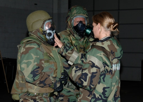 MCCONNELL AIR FORCE BASE, Kan. -- Senior Airman Elyce McConnell, 22nd Civil Engineering Squadron, tests the seal on Staff Sgt. Justin Manning's gas mask, and instructs Sergeant Manning and Master Sgt. Matthew Brosius, 22nd Maintenance Group, on wearing J-list protective gear and the importance of performing buddy checks during Chemical, Biological, Radiological, Nuclear and Explosive training, May 13. Airman McConnell teaches the base CBRNE classes and is responsible for ensuring Airmen attending her classes leave with the knowledge they need to survive in chemical contingency situations. (Photo by Airman Justin Shelton)