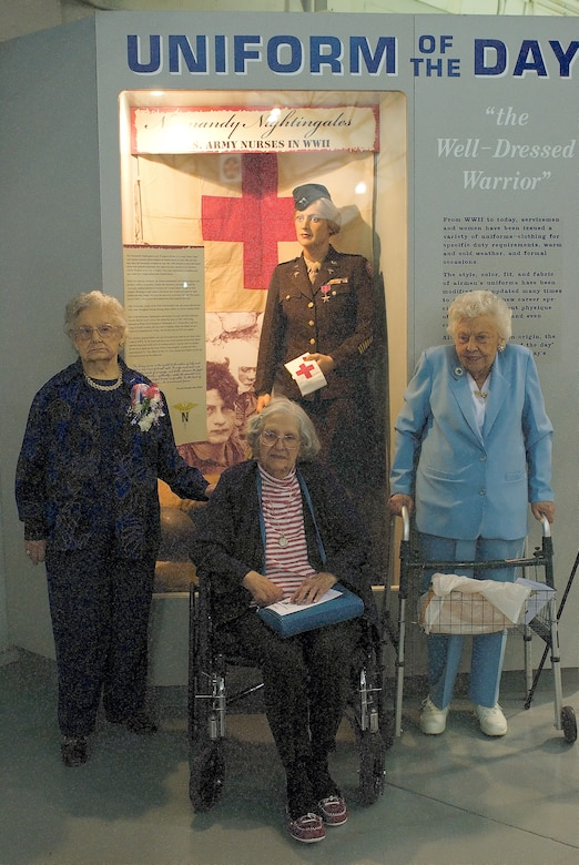(Left to right) Dorothy Lewis, Grace McDonnell, and Mae Bowen pose for a photo in front of the dress uniform and bronze star Mrs. Lewis donated to the Air Mobility Command Museum May 9. These combat nurses are the only three out of 18 Normandy Nightingales alive today. (U.S. Air Force photo/Roland Balik)
