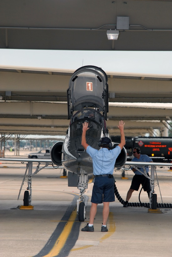 Bill Monk, a T-38 crewman from the 12th Maintenance Division, readies the pilot and aircraft prior to taxi and takeoff for a routine training mission here. (U.S. Air Force photo by Rich McFadden)