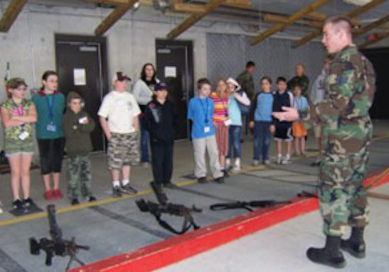 SSgt Thomas A. Addley, 174th Fighter Wing Combat Arms Apprentice gives the children a tour of the firing range