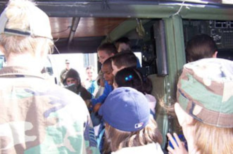 The kids climb in the 274 Air Support Operations Squadron's Humvee.