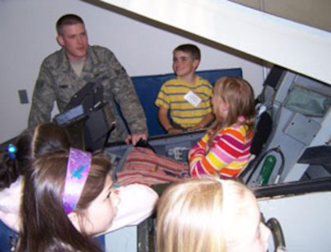 SrA Kyle E. Dimeis, 174th Fighter Wing Survival Equipment Journeyman shows the children the F-16 Flight Simulator