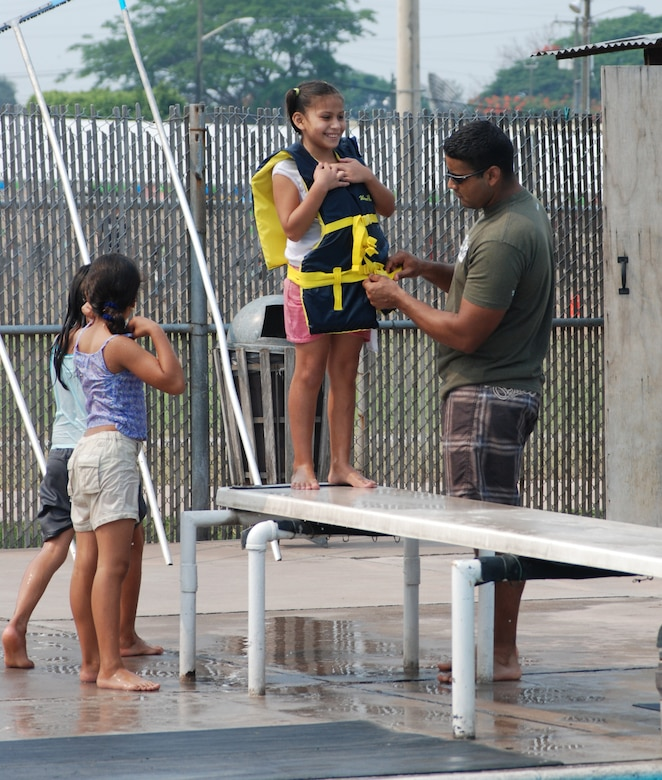 Air Force Staff Sgt. Daniel Santiago, 612th Air Base Squadron civil engineer flight, helps a girl with a life jacket prior to her diving into the pool. More than 100 children and staff from Hogar de Guadalupe Orphanage in El Conejo, Honduras, came to Soto Cano Air Base May 18 for a day of fun and relaxation. (U.S. Air Force photo by Tech. Sgt. John Asselin)