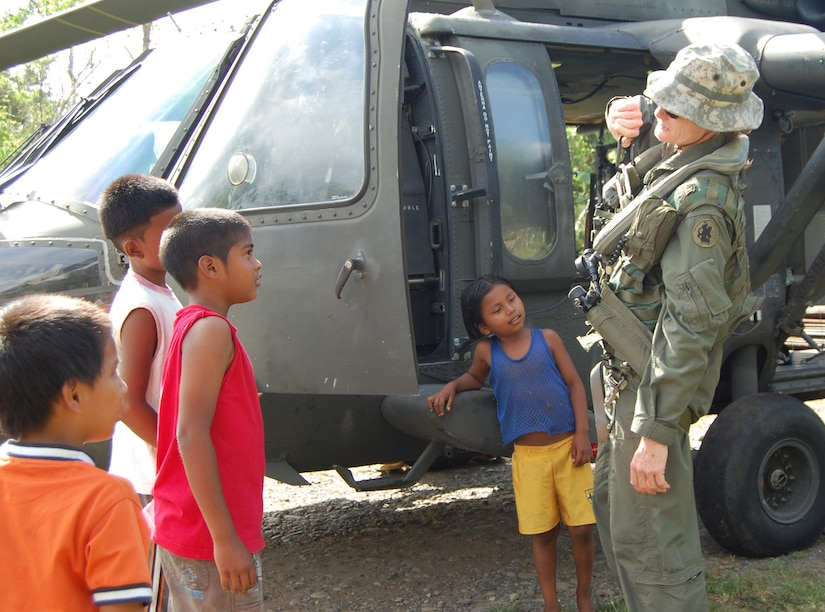 Chief Warrant Officer Kristin Schmid, a UH-60 Blackhawk pilot from Joint Task Force-Bravo, takes a break between lifts to show local Costa Rican children crew equipment and the aircraft. The JTF-Bravo team was in Costa Rica May 9-14 to airlift bridge building materials to three remote areas.