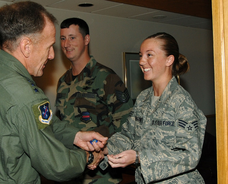 "Lieutenant Gen. Norman Seip, 12th Air Force commander, presents coins to Senior Airman Christine Mirgon and Tech. Sgt. Chad Stoulil May 8 at the Base Operations building. General Seip took time out of his schedule following the annual Air Combat Command commander's conference here to offer his thanks to the 55th Operations Support Squadron, Airlift Validation Flight for their outstanding support. ""The members of this flight are my hidden heroes,"" said Lt. Col. Mohan Krishna, 55th Operations Support Squadron director of operations. ""They get senior leaders where they need to be, long time and within the rules. We really appreciated Lieutenant General Seip taking time from his busy schedule to personally thank these hard working Airmen."" (Courtesy Photo)"