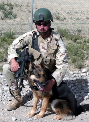 """Staff Sgt. Christopher Dion and his military working dog Dena, both from the 6th Security Forces Squadron, MacDill Air Force Base, Fla., stop for a photo prior to leaving for a mission May 15, 2008, from Bagram Air Base, Afghanistan.  On his first deployment as an MWD handler, Sergeant Dion trained at home station and in the U.S. Air Force Expeditionary Center's Phoenix Warrior Training Course to get ready for to deploy.  In his words, Sergeant Dion says he's """"excited to finally do what I've desired and trained to do for so long -- be an MWD handler.""""  (U.S. Air Force Photo)"""