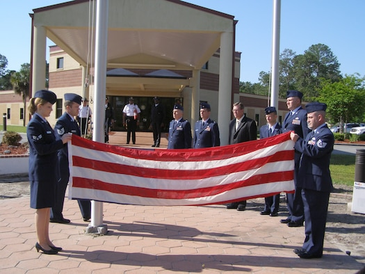 Instructors and staff of the United States Air Force Special Investigations Academy (USAFSIA) gathered at the headquarters building of the Federal Law Enforcement Training Center, Brunswick, Ga., April 14, to do their part for the Air Force Office of Special Investigation's 60th Anniversary ceremony. Folding Flag: Left - SrA Sara McCoy, AFSIA IM; Right - TSgt Charles Meore; NCOIC, AFSIA/CSS; At Flag Pole:  TSgt Phillip Santomauro, Instructor, AFSIA Basic Division. In Rear from Left to Right:  Lt Col Nicholas Mattia, IMA to AFSIA/CC; Major Keith Crook FSC/Instructor; Mr. Jeffrey Thompson, Director, AFSIA Advanced Division; Capt. Brent Heckel, Director, AFSIA Basic Division; CMSgt Walker Cottingham AFSIA Superintendent. (Courtesy photo)